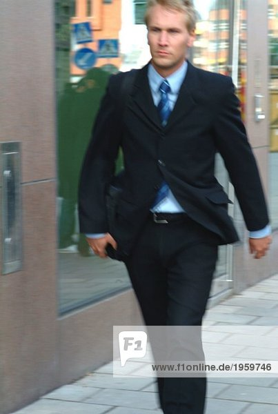 Businessman walking fast in the city