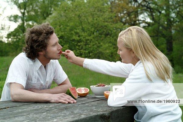 Mädchen füttert Junge mit Erdbeeren