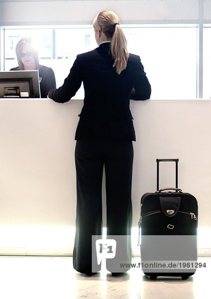 Woman checking in to a hotel