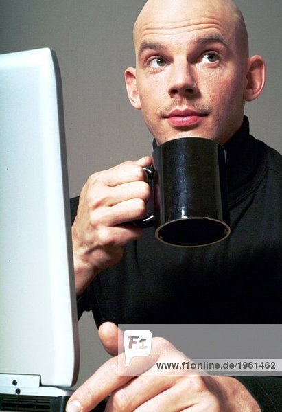 Man with computer drinking coffee
