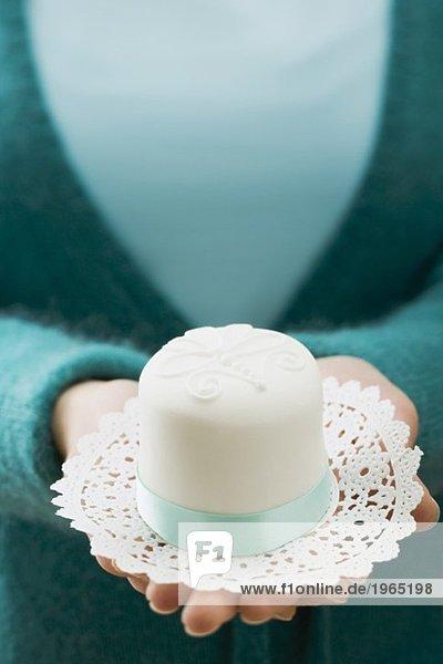 Frau hält weissen Minikuchen auf Tortenpapier