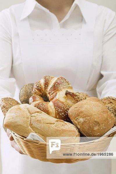 Zimmermädchen serviert verschiedene Brötchen im Brotkorb