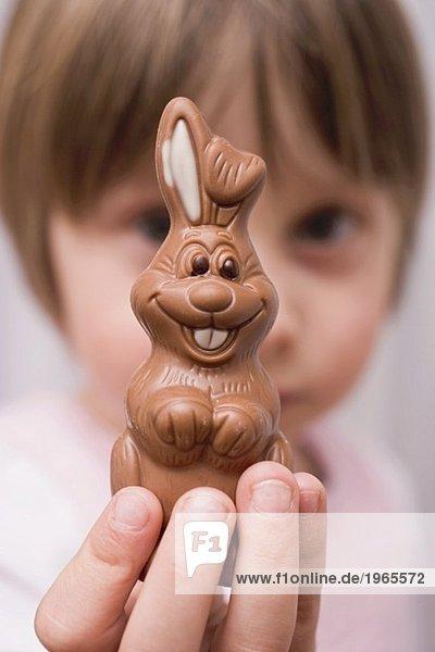 Kind hält Schokoladenosterhasen