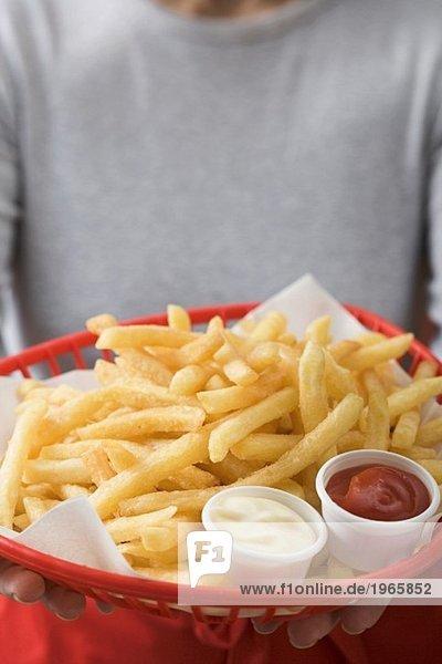 Frau hält Korb mit Pommes frites  Ketchup und Mayonnaise