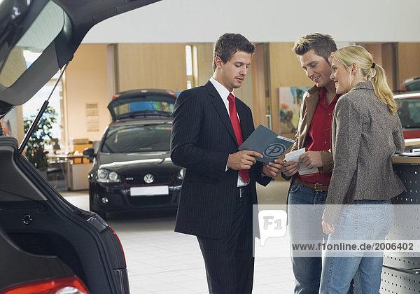 Autohaus  junges Paar im Gespräch mit Verkäufer