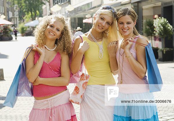 Drei Teenager-Mädchen mit Einkäufen in Einkaufsstraße