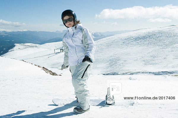 Teenage girl standing with snowboard  smiling at camera  full length portrait