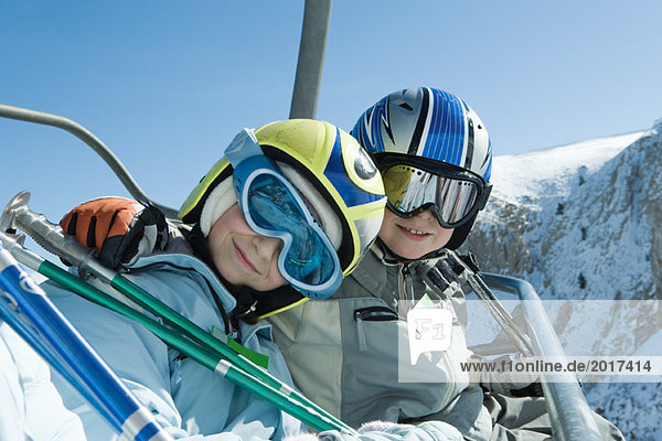 Two young skiers on chair lift  smiling at camera together  portrait