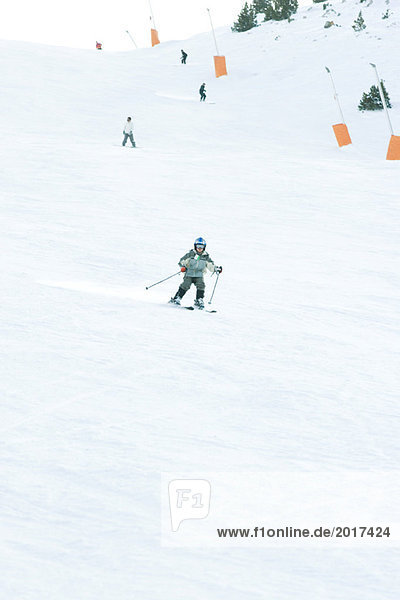 Young skier on ski slope  full length  in the distance