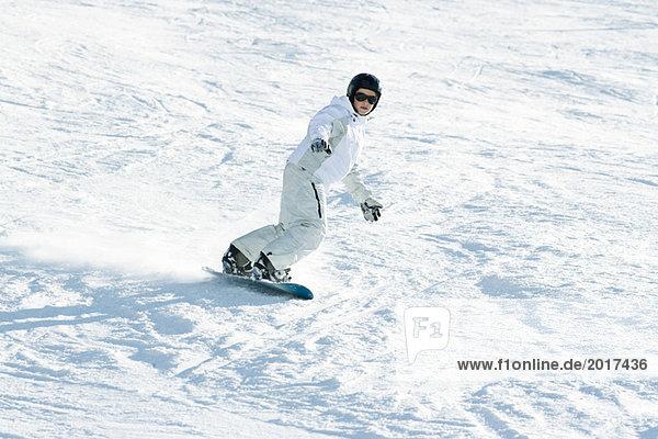 Teenage girl snowboarding down ski slope  full length