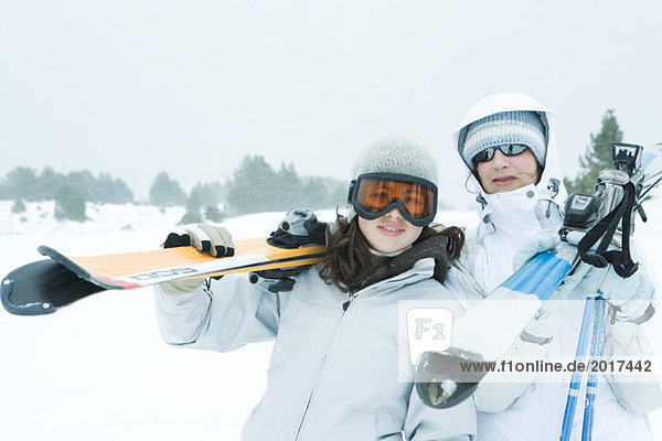 Two young friends carrying skis on shoulders  smiling at camera
