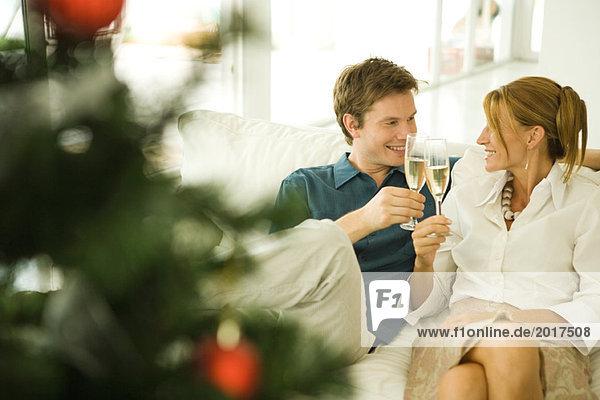 Ein Paar sitzt auf der Couch  macht einen Toast mit Champagner und lächelt sich an.