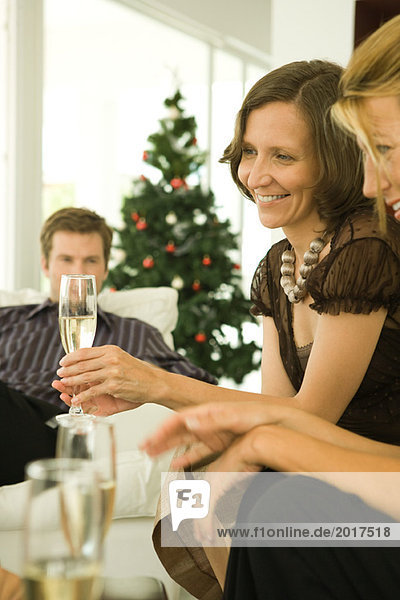 Two women and man sitting on couches  drinking champagne  Christmas tree in background
