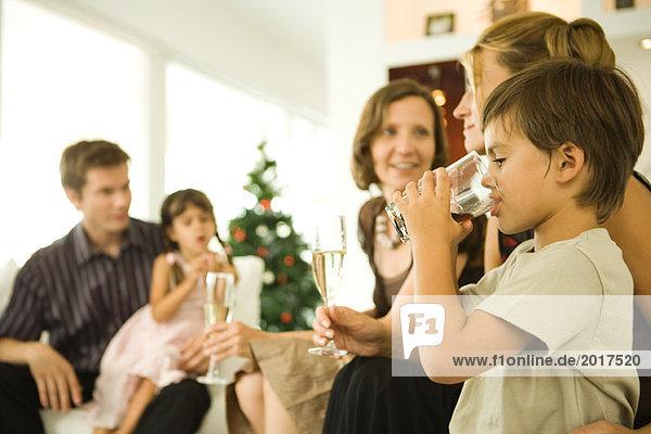 Junge trinkendes Getränk  Erwachsene trinken Champagner  Weihnachtsbaum im Hintergrund
