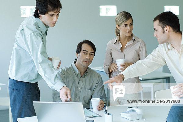 Geschäftspartner um den Laptop versammelt  zwei zeigen auf den Bildschirm