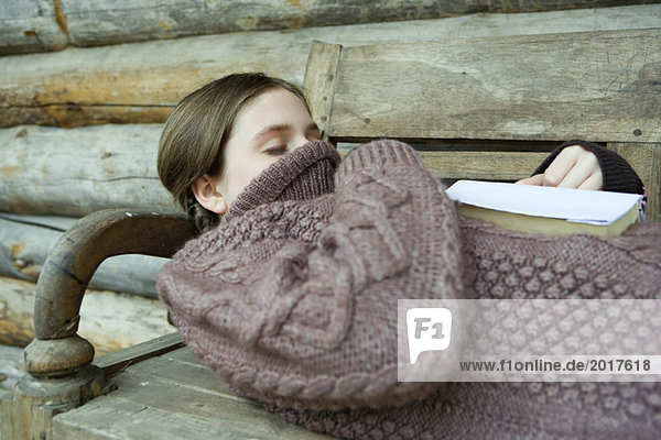 Teen girl sleeping with turtleneck pulled up over face and mouth  book on chest