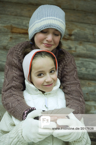 Young friends in winter clothes  one holding cards while the other gives her a hug