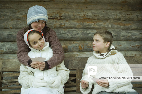 Young friends in winter clothes playing cards
