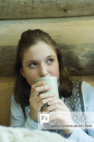 Teen girl drinking hot beverage