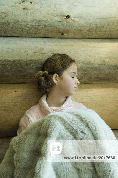 Preteen Mädchen sitzend unter warmer Decke  Augen geschlossen