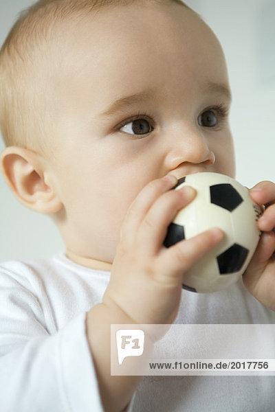 Baby legt Spielzeug Fußball in den Mund  Nahaufnahme