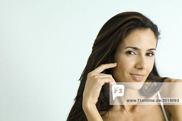 Frau berührt die Wange  lächelt in die Kamera  Porträt