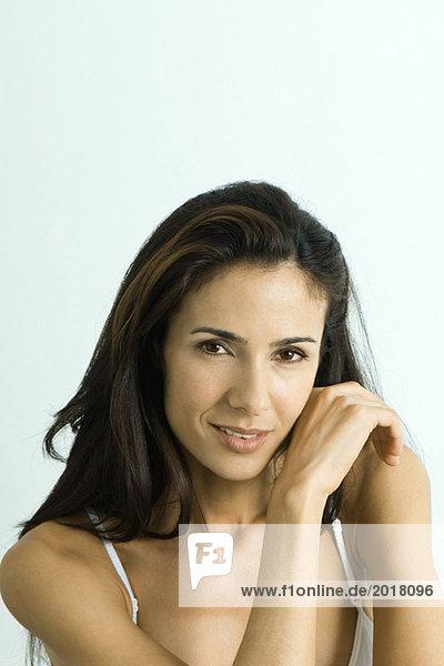 Frau schaut in die Kamera  berührt die Wange mit dem Handrücken  Porträt