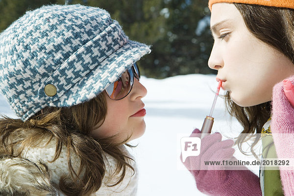 Teenage girl applying lip-gloss  looking at her reflection in friend's sunglasses  both smiling