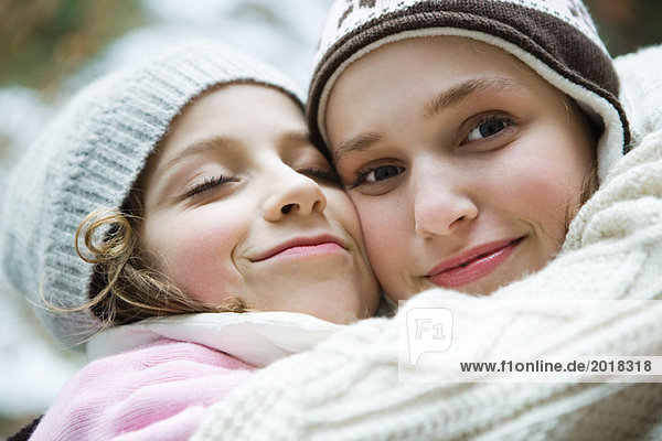 Two sisters embracing  smiling  one closing eyes  the other looking at camera  portrait