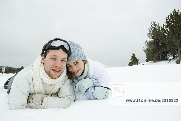 Junges Paar im Schnee nebeneinander liegend  lächelnd vor der Kamera  Porträt
