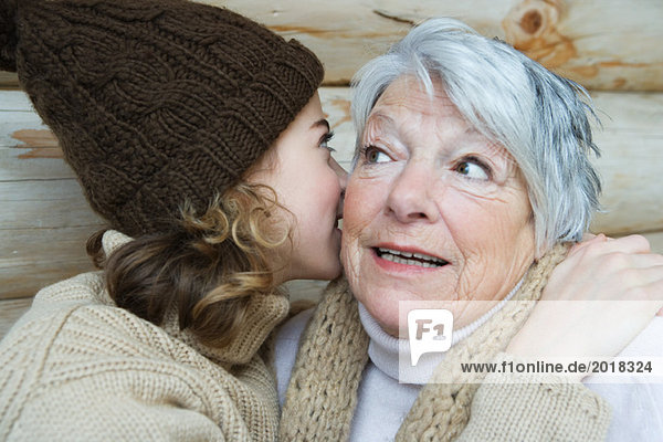Teenage girl whispering into grandmother's ear  portrait
