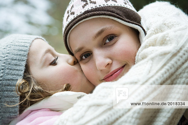 Teenage girl smiling at camera  sister kissing her on cheek  portrait
