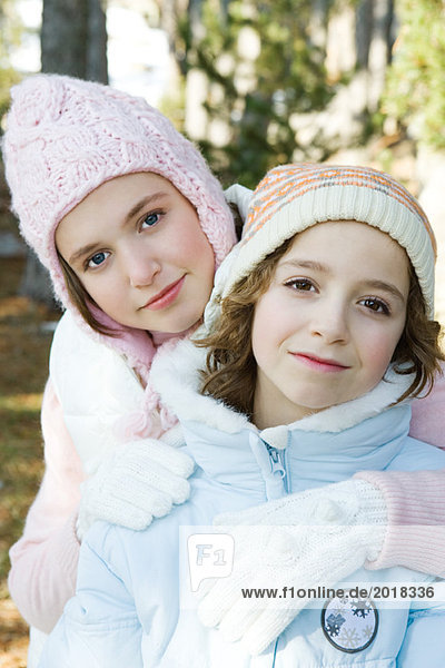 Two young friends smiling at camera  wearing knit hats  one's arm around the other's shoulder  portrait