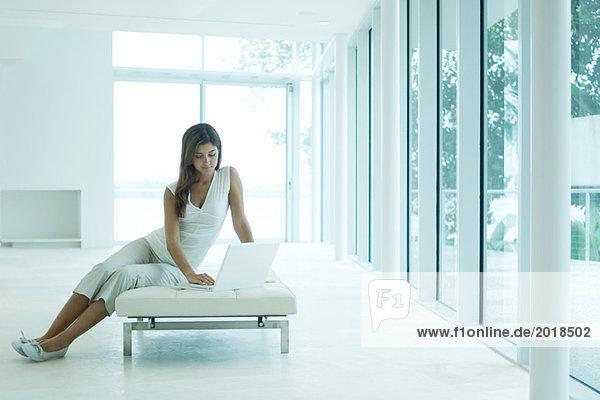 Junge Frau auf dem Sofa sitzend  mit Laptop  Blick nach unten  volle Länge