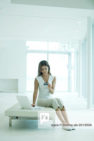 Junge Frau sitzend  mit Laptop-Computer  mit Blick auf Kreditkarte