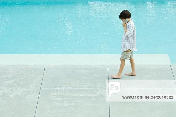 Junge geht neben dem Schwimmbad  benutzt das Handy  schaut nach unten.