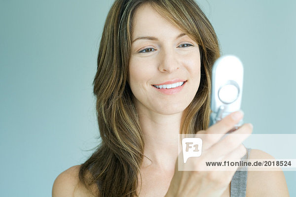 Woman looking at cell phone  smiling  portrait