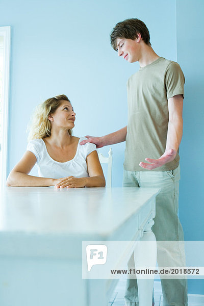 Teen boy standing next to mother sitting at table  hand on her shoulder  gesticulating