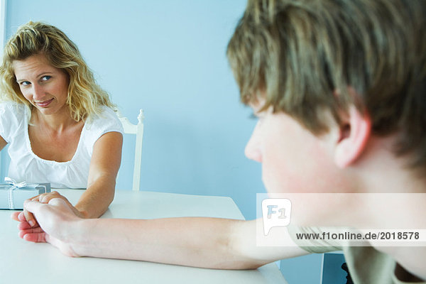 Woman with present looking at teen son  holding his hand