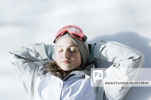 Teenage girl lying on snow with hands behind head and eyes closed