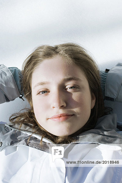 Teenage girl lying on snow with hands behind head  looking at camera