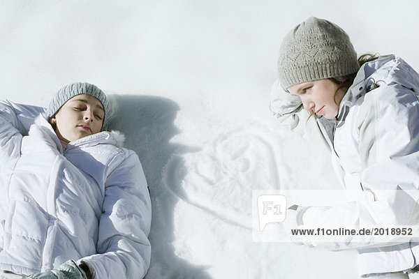 Teenage girls lying on snow  one drawing heart with initials in snow