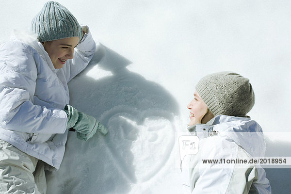 Teenage girls lying on snow  laughing  heart with initials drawn on surface of snow