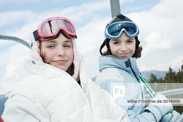 Teenage girl and younger friend taking ski lift  portrait