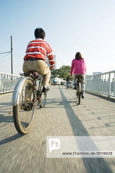 Radfahrer überqueren Brücke  Rückansicht Radfahrer überqueren Brücke, Rückansicht