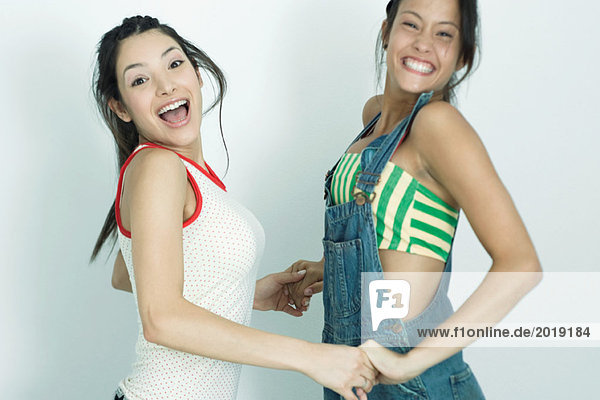 Two young female friends holding hands and jumping in the air  smiling at camera  portrait