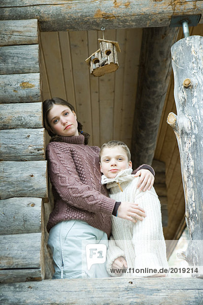 Teen girl embracing little brother  both smiling at camera  portrait