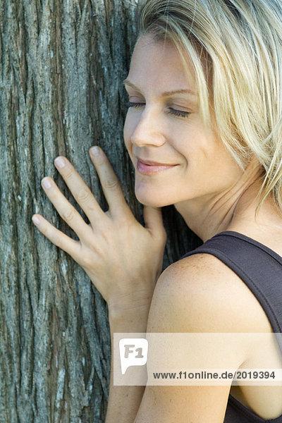 Frau an Baumstamm gelehnt  Augen geschlossen  lächelnd  Ausschnitt  Vollbild
