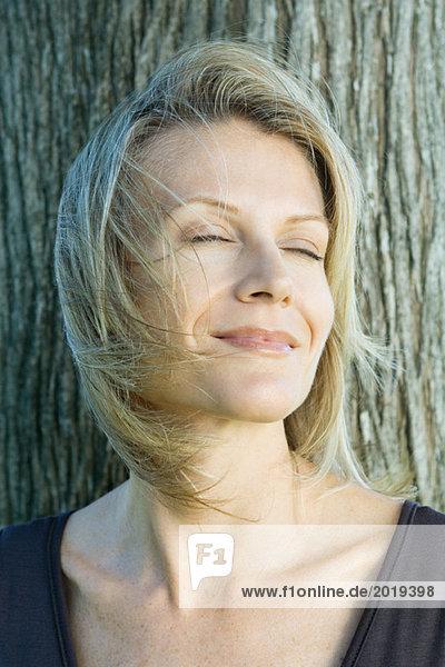 Frau lächelnd  Augen geschlossen  Haare wehend im Wind  Baumstamm im Hintergrund  Kopf und Schultern