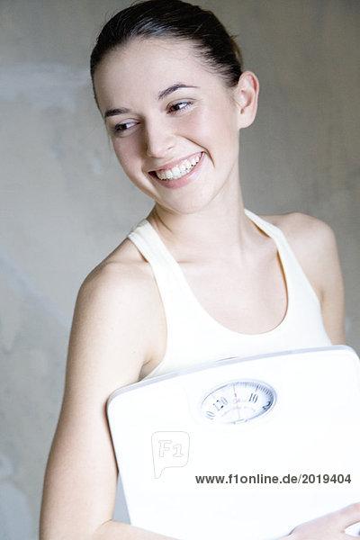 Junge Frau hält Badezimmerwaage  lächelnd  Portrait